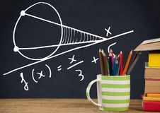 Desk foreground with blackboard graphics of math equations Royalty Free Stock Photography