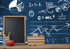 Desk foreground with blackboard graphics of math science diagrams Stock Photo