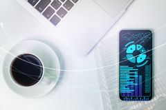 Desk with forex chart on cellphone. Top view of office desk with coffee cup, supplies and forex chart on cellphone screen. Accounting and finance concept. Double Royalty Free Stock Image