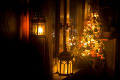 Desk of free space and lamp with xmas tree in home . Christmas lantern in selective focus near window with holiday tree full of. Colored toys and lights. Night stock image