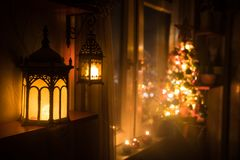 Desk of free space and lamp with xmas tree in home . Christmas lantern in selective focus near window with holiday tree full of. Colored toys and lights. Night royalty free stock photos