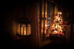 Desk of free space and lamp with xmas tree in home . Christmas lantern in selective focus near window with holiday tree full of. Colored toys and lights. Night royalty free stock photography