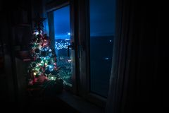 Desk of free space and lamp with xmas tree in home . Christmas lantern in selective focus near window with holiday tree full of. Colored toys and lights. Night stock images