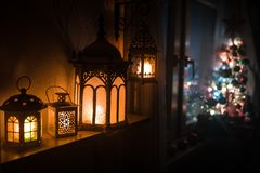 Desk of free space and lamp with xmas tree in home . Christmas lantern in selective focus near window with holiday tree full of. Colored toys and lights. Night royalty free stock photo