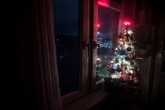 Desk of free space and lamp with xmas tree in home . Christmas lantern in selective focus near window with holiday tree full of. Colored toys and lights. Night stock photography
