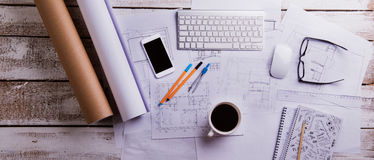 Desk, gadgets and housing projects. Flat lay. Wooden background. Stock Image