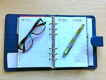 Desk with glasses, diary and pencil Royalty Free Stock Photography