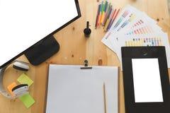 Desk of graphic designer at work - digital tablet, computer screen, color swatch catalog samples for selection. Creativity Editor. Desk of graphic designer royalty free stock images