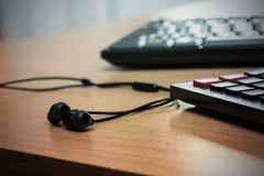 Desk with keyboard, calculator and headphones. Royalty Free Stock Images