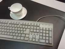 Desk with keyboard and cup Royalty Free Stock Image