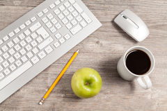 Desk with keyboard and mouse. And green apple Royalty Free Stock Images