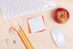 Desk with keyboard, notepaper and an apple Royalty Free Stock Photo