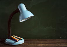 Desk lamp and colored pencils on a wooden surface Royalty Free Stock Images
