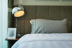 Desk lamp and grey pillow Stock Images