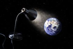 Desk lamp illuminates the Earth. Desk lamp in the outer space illuminates the Earth Stock Photos