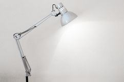 Desk lamp illuminating a white concrete wall Stock Photo