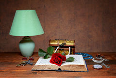 Desk lamp, jewelry and red rose Royalty Free Stock Image