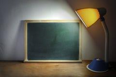 Desk Lamp Shining On Blackboard Stock Photography