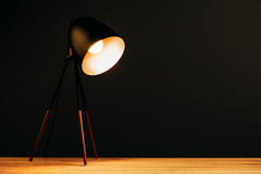 Desk lamp on table in dark office Royalty Free Stock Image