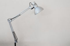 Desk lamp with white concrete wall as background Royalty Free Stock Image