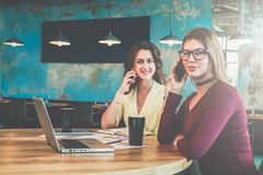 On desk are laptop and documents. Girls working online, learning, shopping. Teamwork. Online education, marketing. Two young smiling businesswomen sitting in Royalty Free Stock Photos