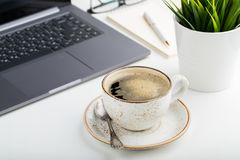 Desk with laptop, eye glasses, notepad, pen and a cup of coffee on a white table. Light background royalty free stock photo