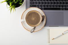 Desk with laptop, eye glasses, notepad, pen and a cup of coffee on a white table. Top view with copy space. Flat lay. Light backgr stock photography