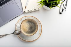 Desk with laptop, eye glasses, notepad, pen and a cup of coffee on a white table. Top view with copy space. Flat lay. Light backgr royalty free stock image