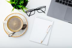 Desk with laptop, eye glasses, notepad, pen and a cup of coffee on a white table. Top view. Flat lay. Light background.  royalty free stock photos