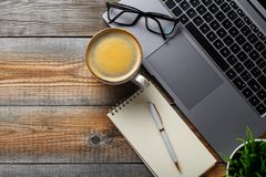 Desk with laptop, eyeglasses, notepad, pen and a cup of coffee on a old wooden table. Top view with copy space. Flat lay. Dark woo royalty free stock photo