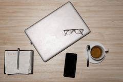 Desk with laptop, eyeglasses, notepad, smartphone, pen and a cup of tea on a wooden table. Top view with copy space. Flat lay -. Image stock photos