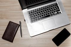 Desk with laptop, eyeglasses, notepad, smartphone, and pen on a wooden table. Top view with copy space. Flat lay - image.  stock image