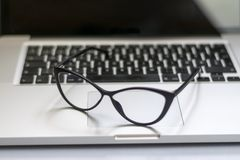 Desk with laptop, glasses and other items royalty free stock images