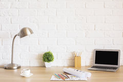 Desk with laptop and sketches. Creative designer desktop with blank laptop screen, plant, coffee cup, sketches, colorful pencils, lamp and other items on white stock photography