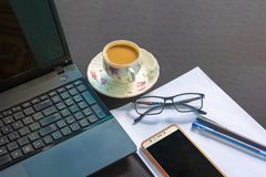Desk with laptop, smart phone, notebooks, pens, eyeglasses and a cup of tea. royalty free stock image