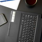 Desk with laptop, smart phone, notebooks, pens, eyeglasses and a cup of tea. Side angle view stock photos