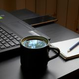 Desk with laptop, smart phone, notebooks, pens, eyeglasses and a cup of tea. Side angle view royalty free stock photos