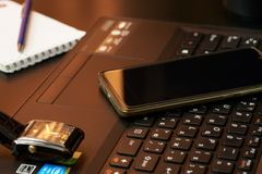 Desk with laptop, smart phone, notebooks, pens, eyeglasses and a cup of tea. Side angle view royalty free stock images