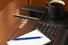 Desk with laptop, smart phone, notebooks, pens, eyeglasses and a cup of tea. Side angle view stock images