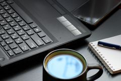Desk with laptop, smart phone, notebooks, pens, eyeglasses and a cup of tea. Side angle view stock photo
