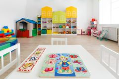 Desk for classes in bright white game room in the kindergarten. Desk for lessons with toys in bright white game room in the kindergarten. Close up Royalty Free Stock Image