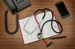 Desk of a medicine doctor. Calendar, phones, stethoscope Royalty Free Stock Image