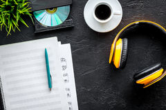 Desk of musician with blank paper and headphones for songwriter work on dark background top view mockup. Desk of musician with blank paper and headphones for stock photos