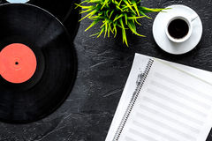 Desk of musician or dj with vynil records and blank paper for songwriter work on dark background top view mockup. Desk of musician or dj with vynil records and royalty free stock photography