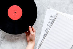Desk of musician or dj with vynil records and blank paper for songwriter work on stone background top view mockup. Desk of musician or dj with vynil records and royalty free stock photo