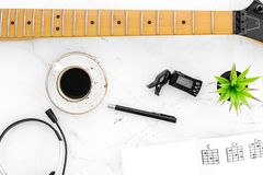 Desk of musician for songwriter work with headphones, keyboard, guitar and notes marble background top view. Desk of musician for songwriter work with headphones royalty free stock photography
