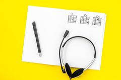 Desk of musician for songwriter work with headphones and notes yellow background top view. Desk of musician for songwriter work with headphones and notes on stock photography