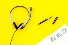 Desk of musician for songwriter work with headphones and notes yellow background top view. Desk of musician for songwriter work with headphones and notes on stock photos
