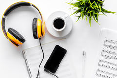 Desk of musician for songwriter work with headphones and smartphone on white background top view mockup. Desk of musician for songwriter work set with headphones stock photo