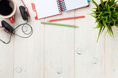 Desk with notepad, coffee and headphones Royalty Free Stock Images